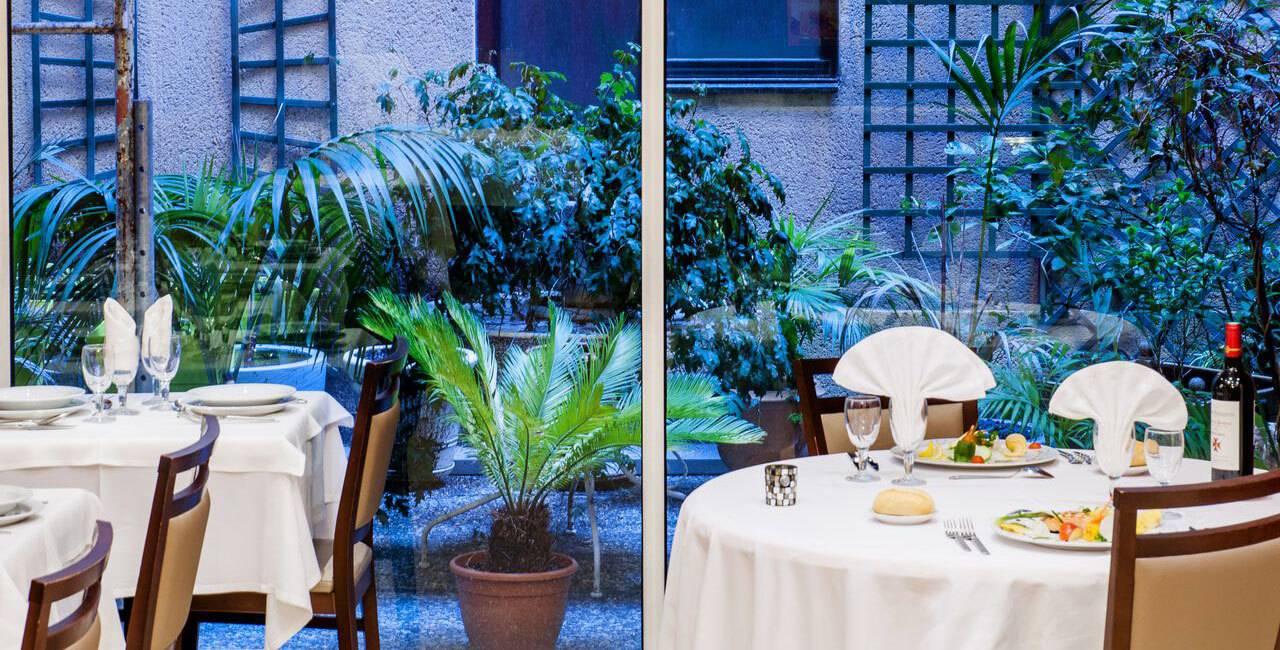 Table du restaurant avec vue sur notre espace de vie arboré et fleuri en extérieur, restaurant lourdes, Hôtel Saint-Sauveur.